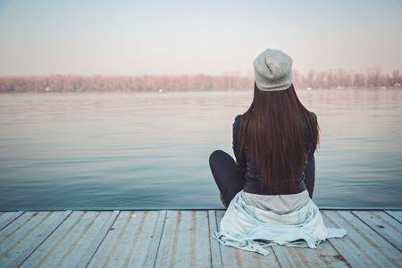 40838941-girl-sitting-on-pier-and-lookingat-the-river